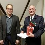 Bürgermeister Björn Warmer übergibt Hans-Gunther Bostel die Ehrengabe der Stadt Reinbek für 40 Jahre aktive Mitgliedschaft in der FF Ohe